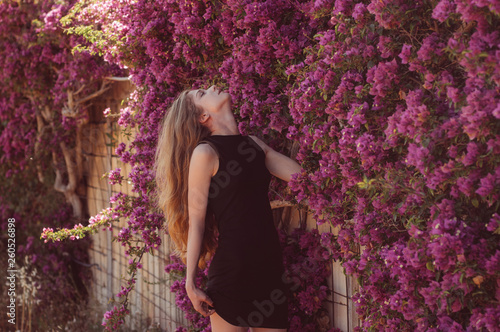 Photographie Portrait of girl among purple bougainvillaea