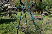 Abandoned Playground Old Swings And Merry-go-round
