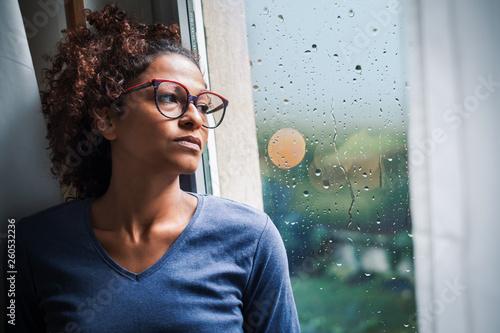 Fotografija Lonely black woman near window thinking about something