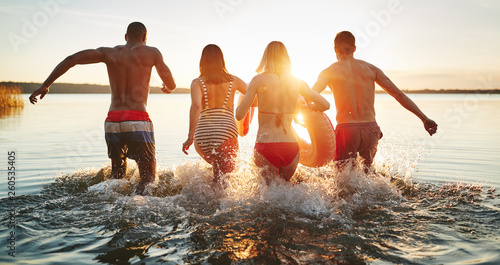 Fotografie, Obraz  Diverse young friends splashing into a lake together at sunset