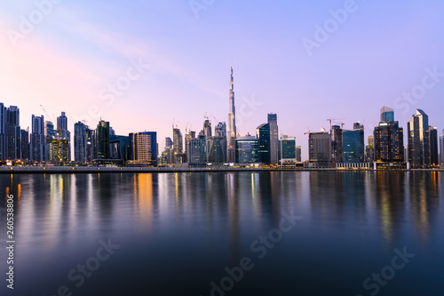 Tuinposter Dubai Panoramic view of the illuminated Dubai skyline during sunset with the magnificent Burj Khalifa and many others skyscrapers reflected on a silky smooth water flowing in the foreground. Dubai.