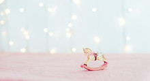 Vintage Christmas Tree Toy Porcelain Figurine Of A Rocking Horse Standing On The Pink Tablecloth Against The Background Of Blurred Lights. Festive Layout. Wide Banner. Soft Selective Focus. Copy Space