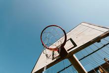 Old Basketball Hoop Against Blue Sky