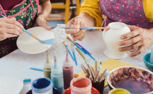 Woman Coloring Handmade Dishes Using Brush And Color