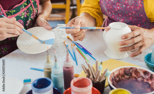 Canvas Print Woman coloring handmade dishes using brush and color