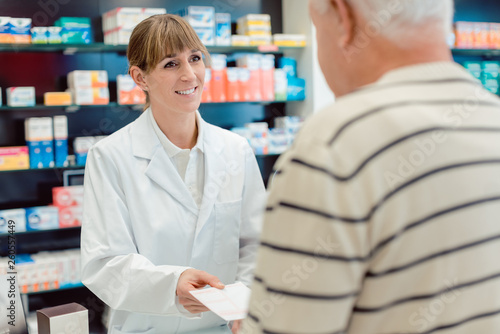 Poster Pharmacie Pharmacist taking prescription slip from senior man