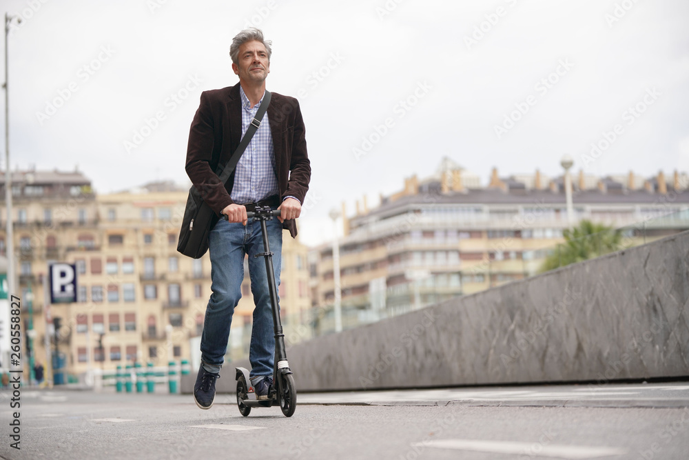Fototapety, obrazy: Businessman on daily commute riding micro scooter