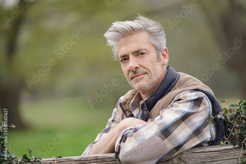 Cuadros en Lienzo Attractive farmer leaning on fence looking at camera