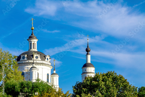Fotografia  The domes of the Christian church against the blue sky and green trees