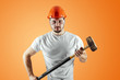 Bearded Man in a helmet holds a sledgehammer on an orange background. Concept of construction, contractor, repair.