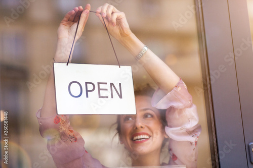 Foto Woman holding open sign in cafe