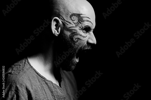 Photo  tattoo on the face,  man with a tattoo,  brutal bearded guy, studio portrait of