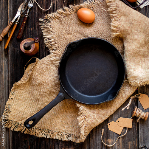 Fotografía  Overhead shot of cast-iron pan standing on sackcloth on wooden rustic table