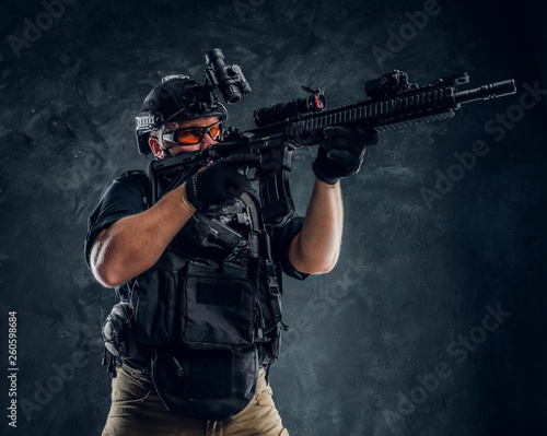 Special forces soldier holding an assault rifle with a laser sight and aims at the target Fototapeta