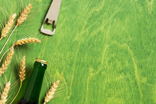 Green Background With Beer Bottle, Opener And Ears Of Wheat