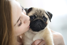 Blonde Girl With Kisses And Holds Pug Puppy