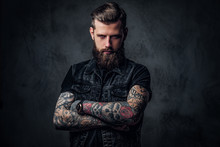Portrait Of A Stylish Bearded Guy With Tattooed Hands. Studio Photo Against Dark Wall