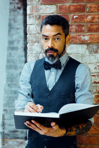 Photo Man in bow tie holding pen and notebook
