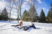 Two Friends Making Snow Angels During Winter
