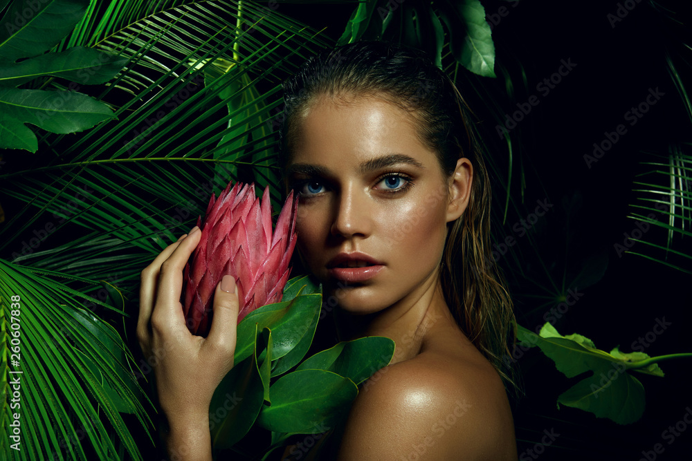 Fototapeta A beautiful tanned girl with natural make-up and wet hair stands in the jungle among exotic plants.