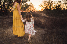 Young Girl Holding Mothers Hand While Walking Away In California Field
