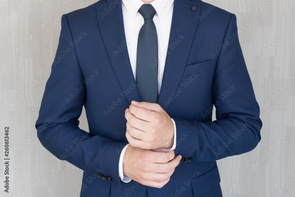 Fototapeta Torso of anonymous businessman wearing beautiful fashionable classic navy blue suit against grey backgound.
