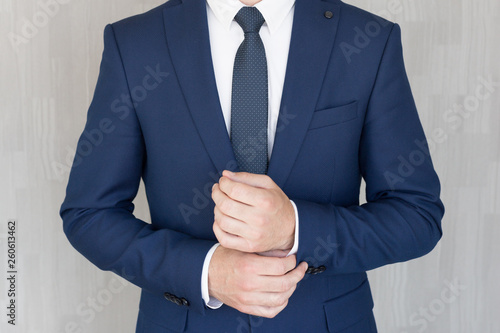 Obraz na płótnie Torso of anonymous businessman wearing beautiful fashionable classic navy blue suit against grey backgound