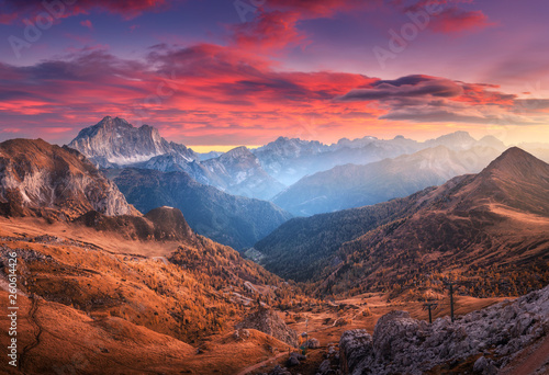 Foto auf Gartenposter Gebirge Colorful red sky with clouds over the beautiful mountains in fog at sunset in autumn. Dolomites, Italy. Landscape with mountain range, hills with orange grass, trees, sky with orange sunlight. Travel