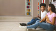 canvas print picture Smiling teenage couple sitting on floor in library