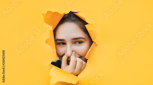 Fototapeta Ridiculous teenage girl closes her nose with her fingers because she feels a fetid odor. Yellow background, copy space. The concept of bloating, indigestion, farting. obraz na płótnie
