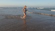 4K slow motion view of a beautiful young woman running in the shallow water on beach, South Africa
