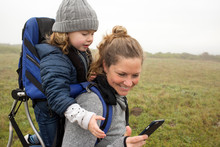 A Mother And Daughter Hiking Together And Looking At A Cellular Device.