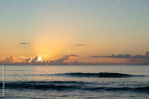 Ostatnie promienie dnia świeciły z chmur, gdy słońce zachodzi na Ocean Spokojny w Maui na Hawajach.