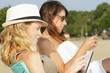 two young ladies on the beach using electronic devices