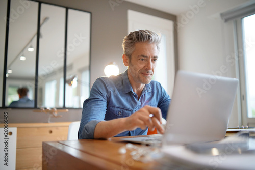 Fototapeta Mature man working from contemporary home