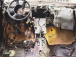 Disassembled console in car with lots of colorful wires; many vehicles parts; repairing electronics, troubleshooting; rudder and front panel in the automobile; renovating in garage; man's leisure time