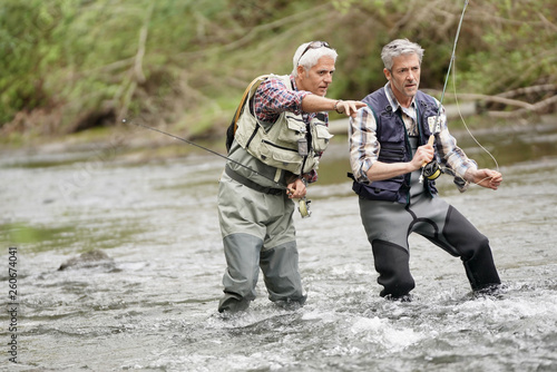 Tablou Canvas Fly fishing expert guiding novice in river