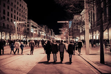Asphalt Road Leading Into The City At Night. Crowd Of People In A Shopping Street. Modern Competitive Life Concept. Unrecognizable Mass Of People Walking In The City - Image.