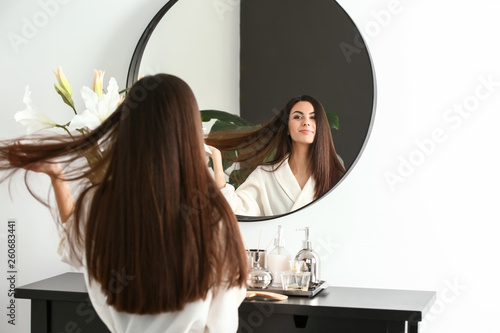 Obraz Beautiful young woman with healthy long hair looking in mirror at home - fototapety do salonu