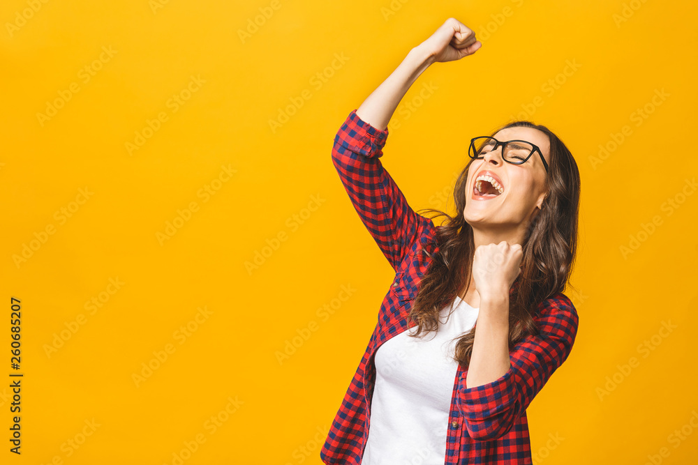 Fototapety, obrazy: Winning success woman happy ecstatic celebrating being a winner. Dynamic energetic image of multiracial Caucasian Asian female model isolated on yellow background waist up.