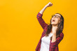 canvas print picture - Winning success woman happy ecstatic celebrating being a winner. Dynamic energetic image of multiracial Caucasian Asian female model isolated on yellow background waist up.