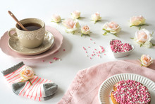 Rusk With Pink And White Aniseed, Dutch Muisjes. Traditional Treat When A Baby Girl Is Born In The Netherlands. Cup Of Tea And Roses On White Table.