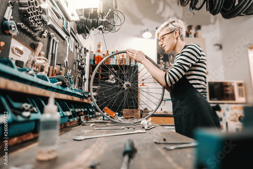 Fotomural Cute Caucasian female worker holding and repairing bicycle wheel while standing in bicycle workshop