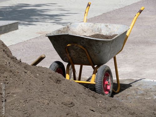 Fotografía  Wheelbarrow with ground near the heap of soil