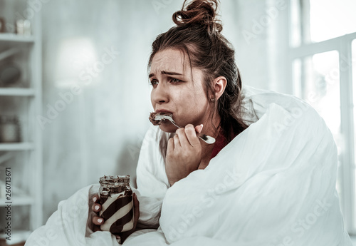 Slika na platnu Woman eating chocolate pasta because of being stressed