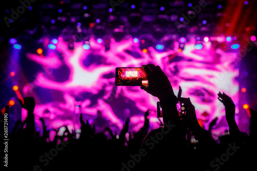 Smartphone in hand at a concert, purple light from stage - 260721490