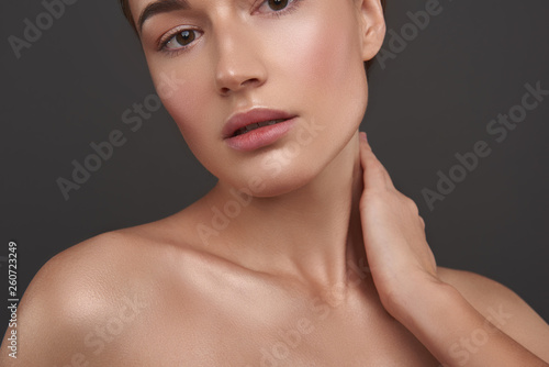 Fotomural Beautiful young woman with perfect smooth skin touching her neck