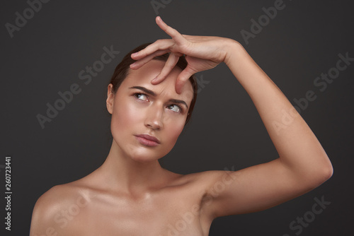Stampa su Tela Beautiful young woman touching skin on her forehead and looking away