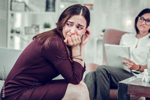 Overemotional woman crying while sharing problem with therapist Wallpaper Mural