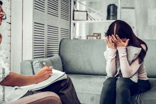 Foto  Dark-haired young woman hiding her face from psychologist